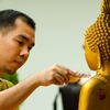 photo: Scented Statue - A Thai man gently pours a small bottle of perfume onto a Buddha statue for Songkran.